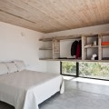 Bed in White Pillows and Bedcover Also Beside the Wooden Storage Goods at the House on the Beach