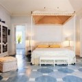 Bedroom with Four Poster Bed Geometric Floor Yellow Accent and Ottoman Completed the Area