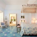 Bedroom with Four Poster Blue and White Bed Geomatric Floor and the Ottoman Add Perfect the Decor