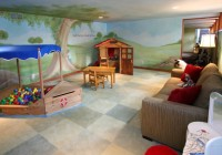 Space and Tree Mural and Wooden Chairs Beside the Sofa with Red Pillows